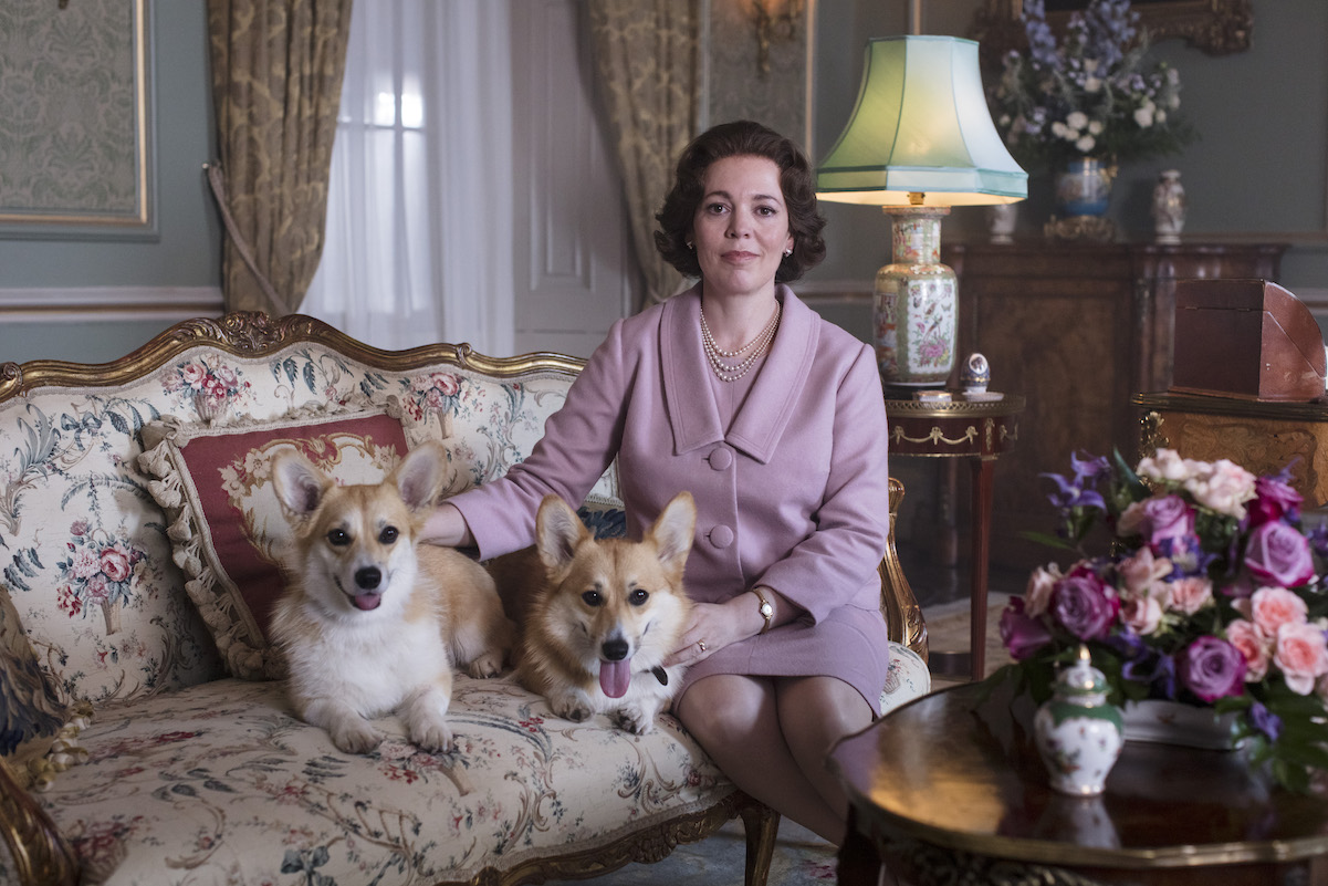 Olivia Colman as Queen Elizabeth II posing with dogs in 'The Crown' Season 3 Episode 2