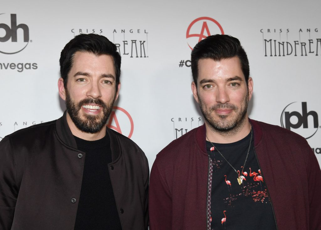 (L-R) Drew Scott and Jonathan Scott smiling in front of a white background