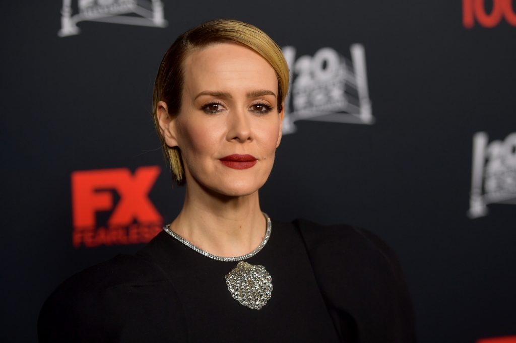 Sarah Paulson slightly smiling in front of a black background