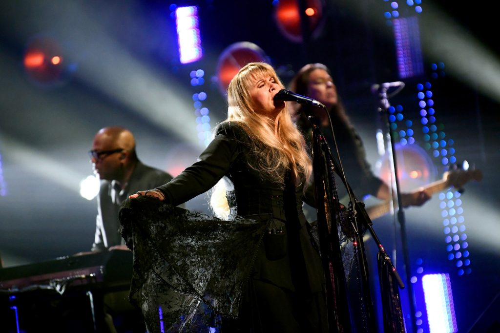 Stevie Nicks singing on stage, arms outstretched