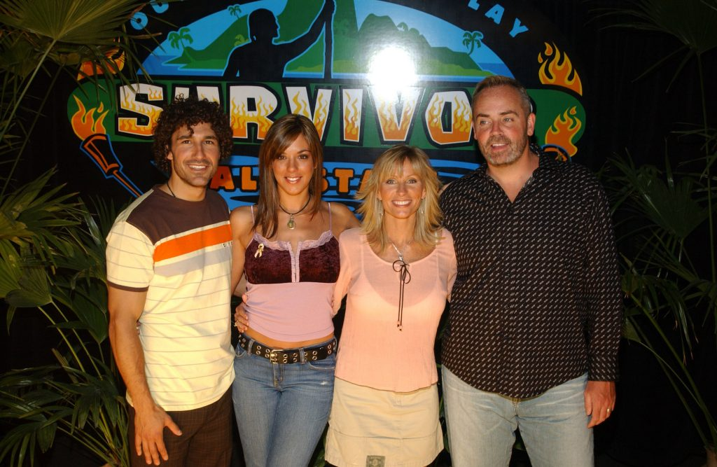 (L-R) Ethan Zohn,Jenna Morasca , Kathy Wesson and Richard Hatch smiling in front of a 'Survivor' logo