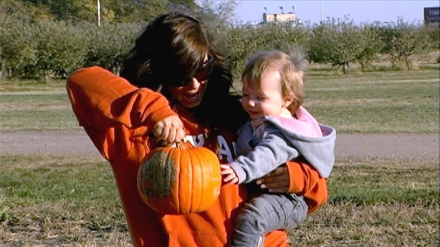 Chelsea Houska and daughter Aubrey smiling and looking at a pumpkin