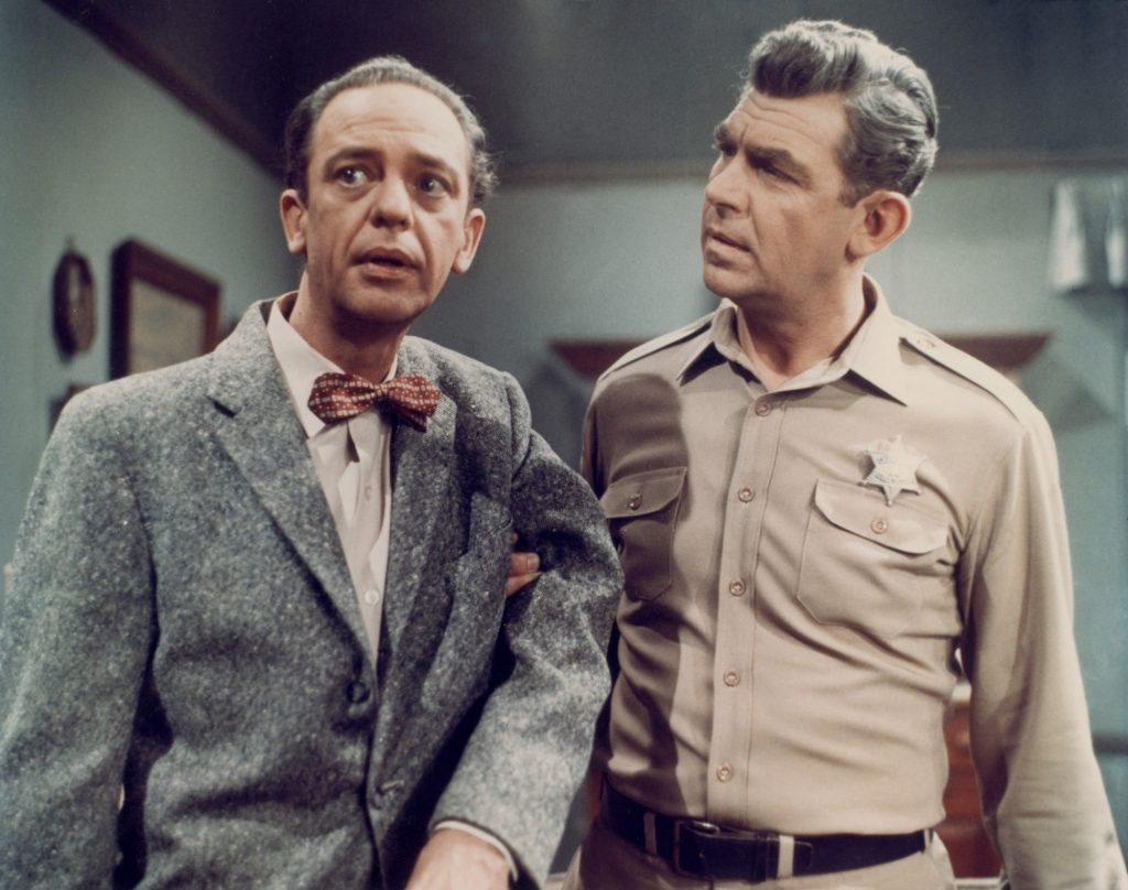 (L-R) Don Knotts as Deputy Barney Fife looking off to the left and Andy Griffith as Sheriff Andy Taylor looking at Knotts