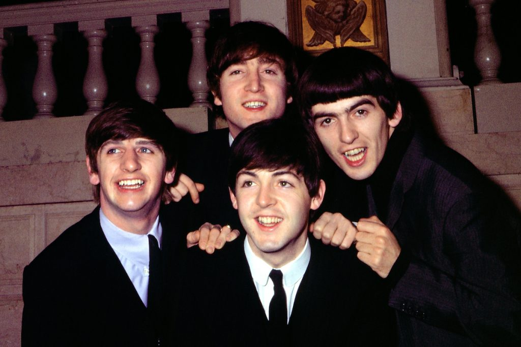 """Rock and roll band """"The Beatles"""" pose for a portrait wearing suits in circa 1964."""