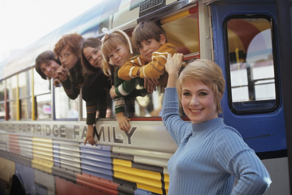 (L-R) David Cassidy, Danny Bonaduce, Susan Dey, Suzanne Crough, Jeremy Gelbwaks, and Shirley Jones with the painted bus in color