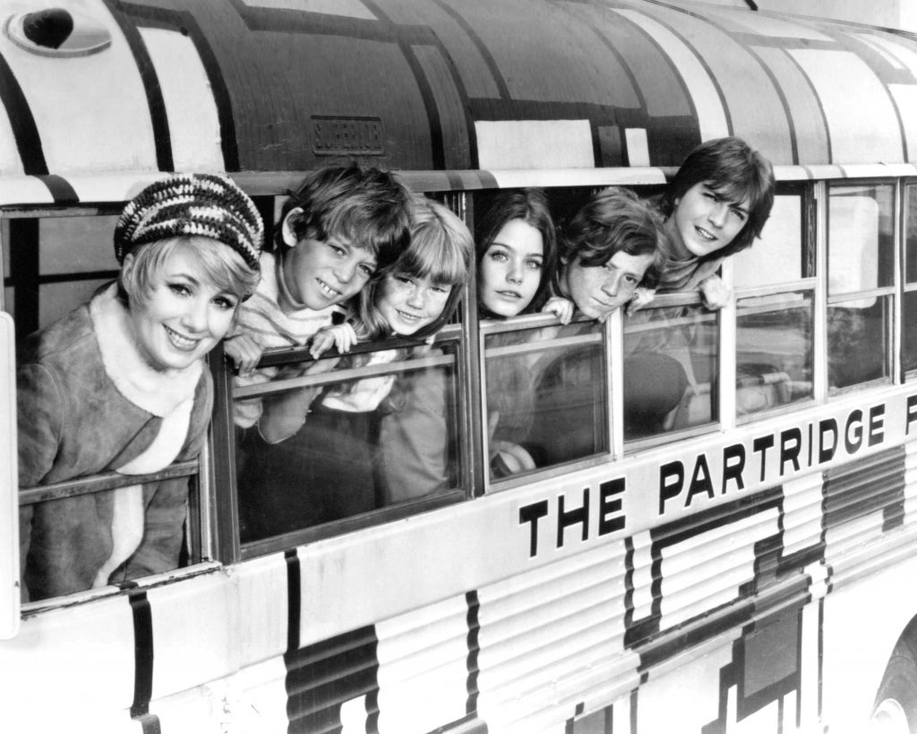 (L-R) Shirley Jones, Jeremy Gelbwaks, Suzanne Crough, Susan Dey, Danny Bonaduce and David Cassidy leaning out of schoolbus windows, in black and white