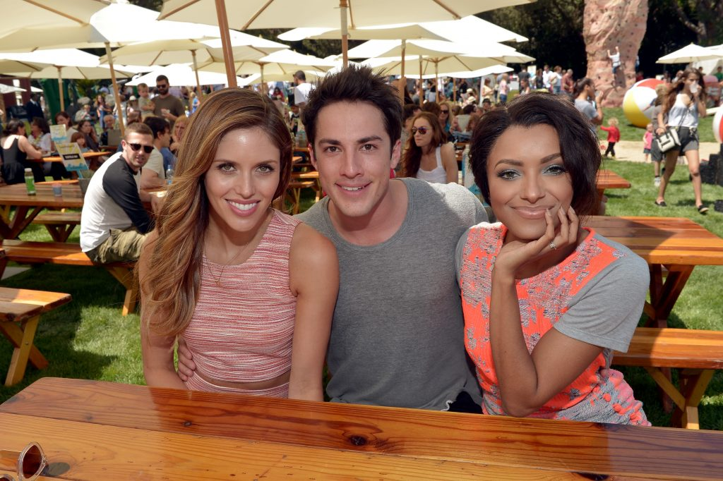 (L-R) Kayla Ewell, Michael Trevino, and Kat Graham smiling at a picnic table