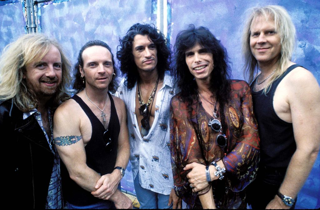 Aerosmith in front of a metal barrier
