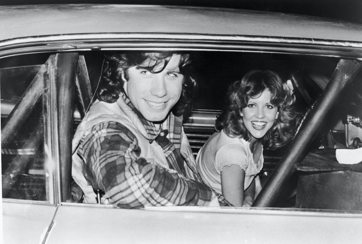 John Travolta and Nancy Allen pose in a car on the set of the film, 'Carrie,' 1976