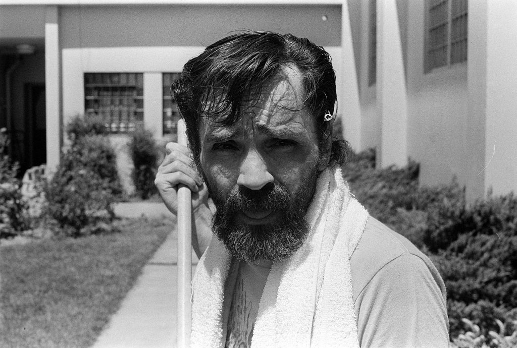 Charles Manson in front of a building