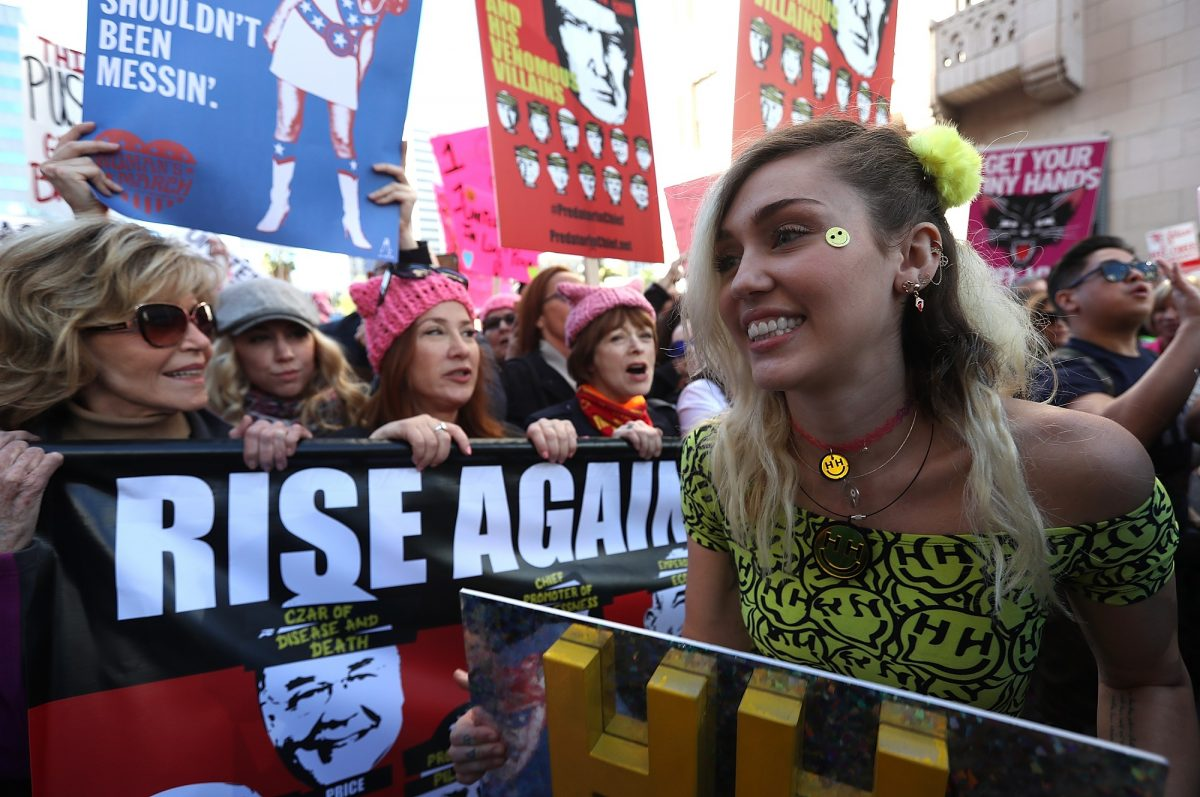 Miley Cyrus (R) marches during the Women's March on January 21, 2017, in Los Angeles, California.  Tens of thousands of people took to the streets of Downtown Los Angeles for the Women's March in protest after the inauguration of President Donald Trump.