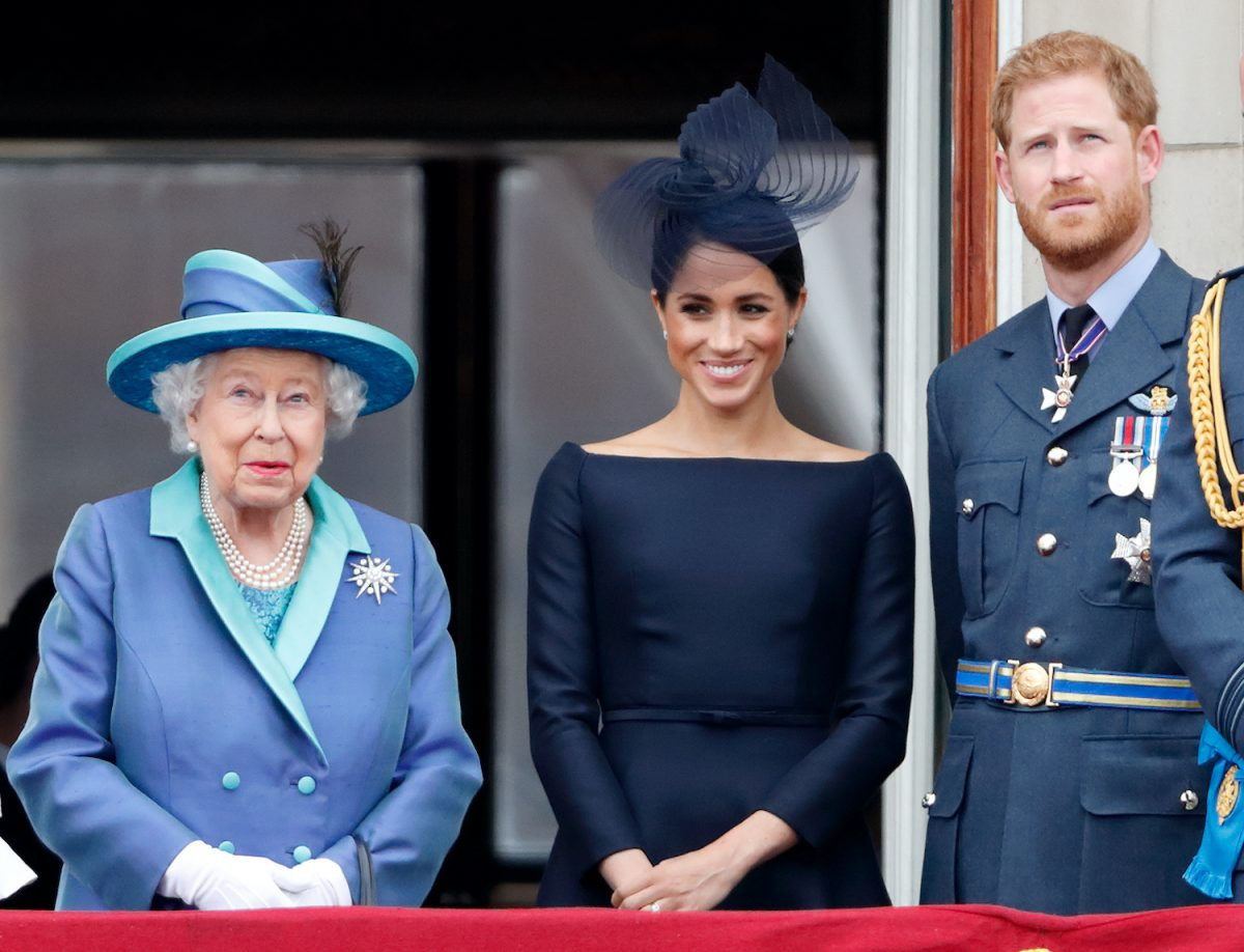 Queen Elizabeth II, Meghan Markle, and Prince Harry watch a flypast to mark the centenary of the Royal Air Force from the balcony of Buckingham Palace