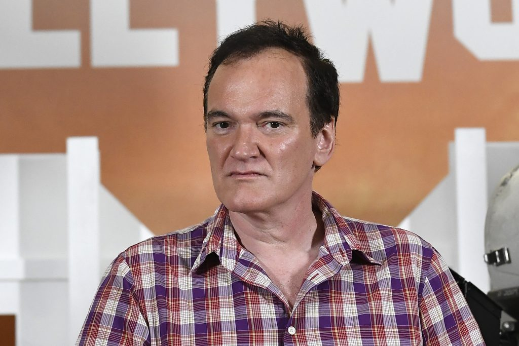 Quentin Tarantino in front of a poster