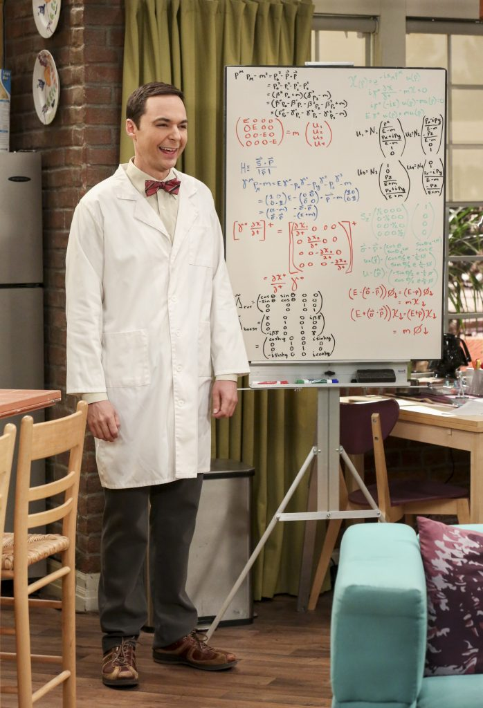 Jim Parsons as Sheldon Cooper stands next to his whiteboard