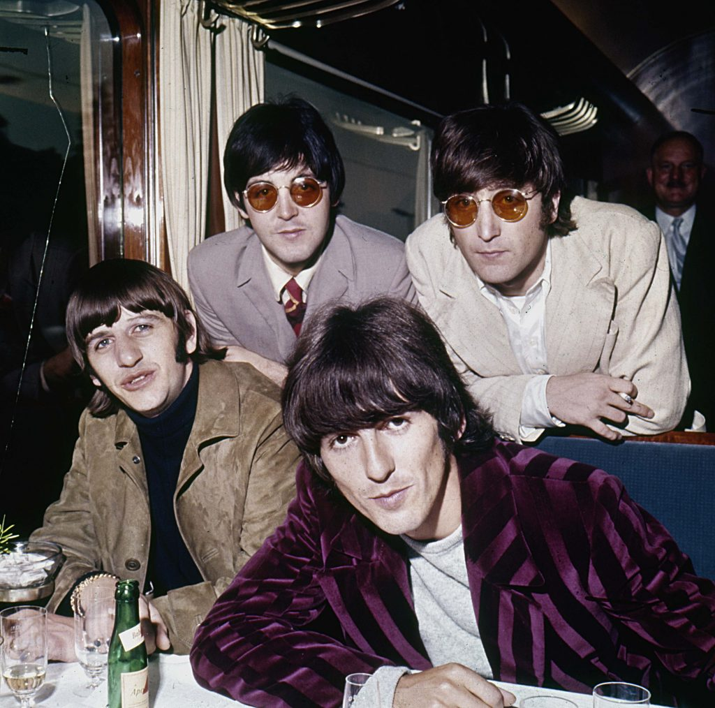 The Beatles wearing suits near a bottle