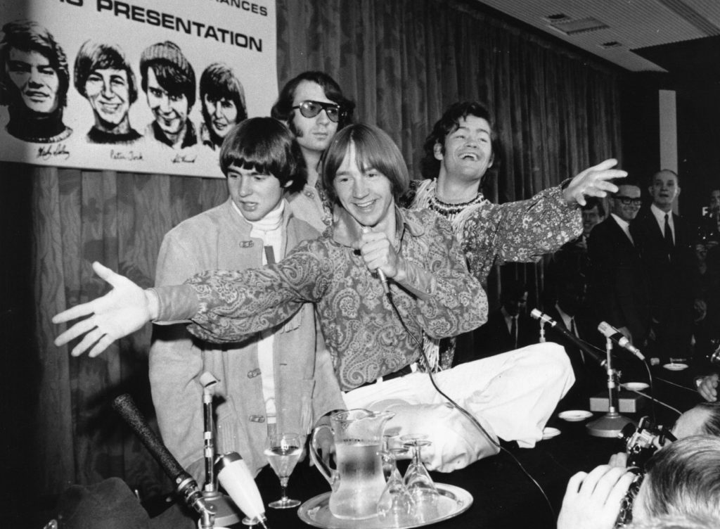 The Monkees in front of a poster of The Monkees
