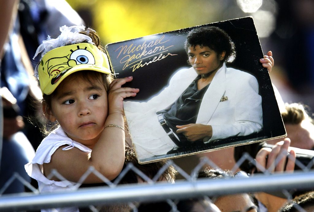 A child wearing a SpongeBob SquarePants hat holding a copy of Thriller