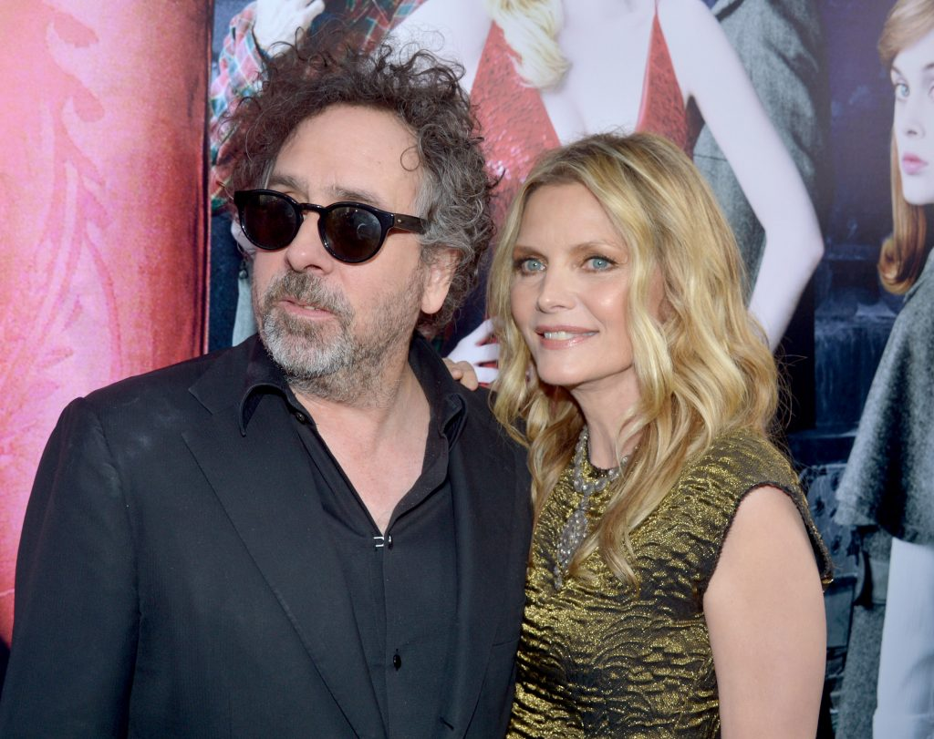 Tim Burton and Michelle Pfeiffer in front of a poster