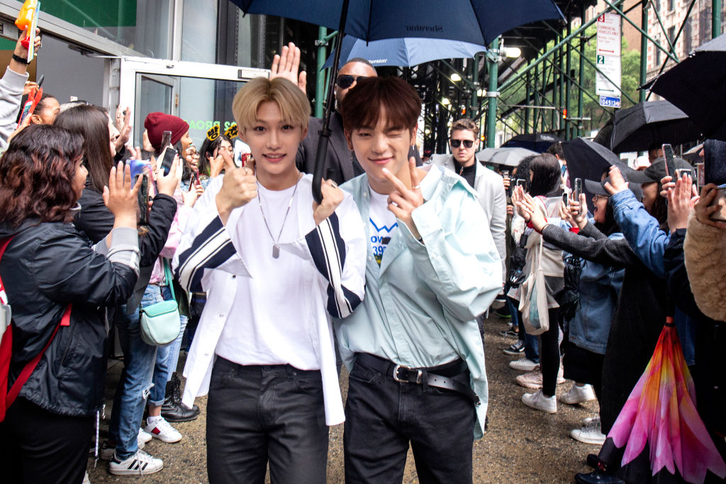 Felix and Woojin of Stray Kids with an umbrella