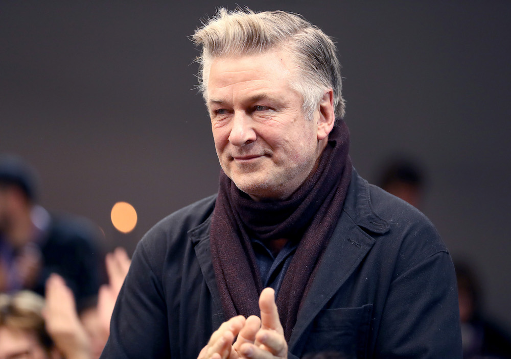 Alec Baldwin looking to the left in front of a blurred background
