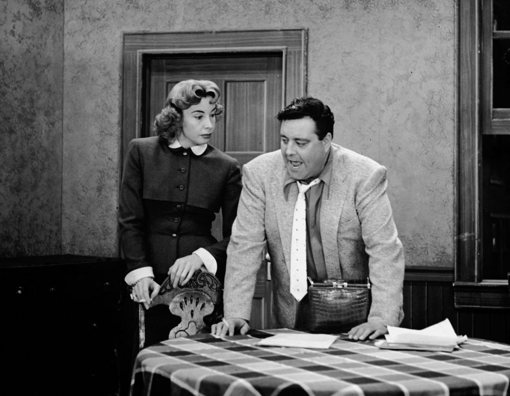 Audrey Meadows as Alice Kramden and Jackie Gleason as Ralph Kramden stand in the kitchen on the set of 'The Honeymooners'