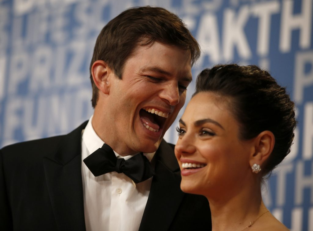 Ashton Kutcher laughs with his wife, actor Mila Kunis