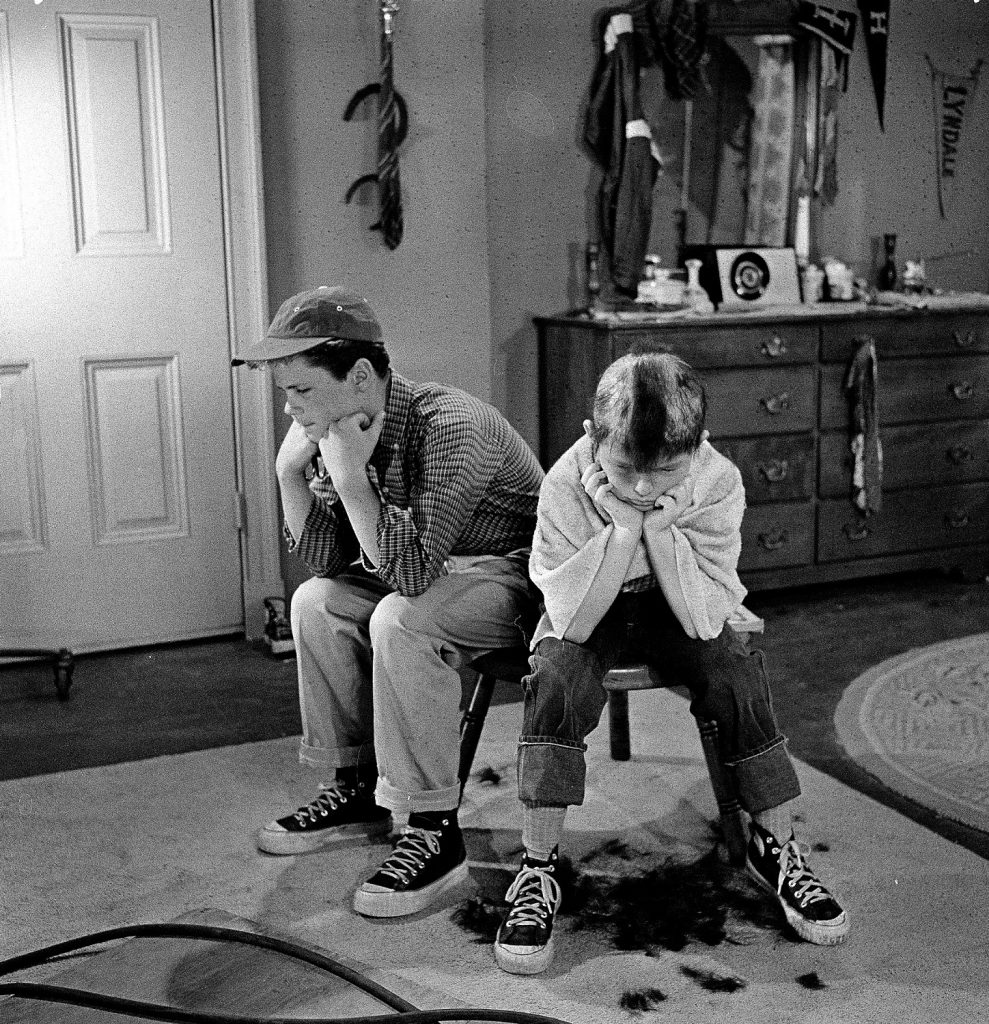 Tony Dow as Wally Cleaver and Jerry Mathers Beaver Cleaver, sit on a stool togethe