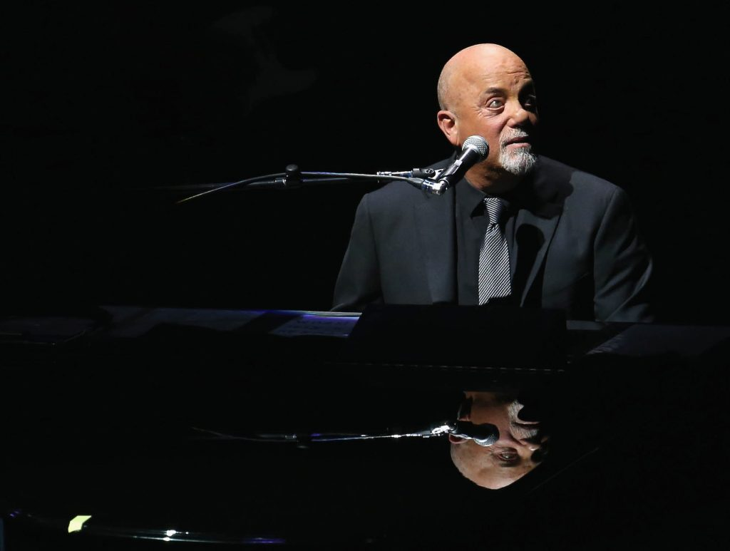 Billy Joel looking off to the side, sitting at a piano, looking to the right
