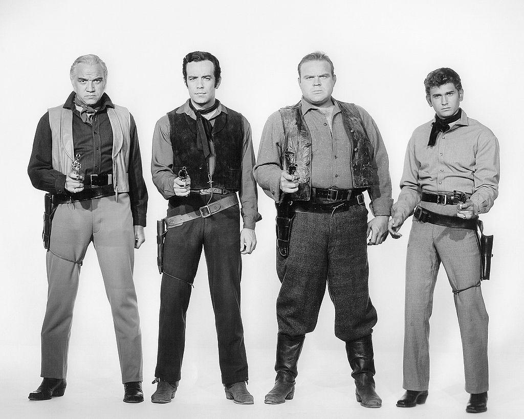 (L-R) Lorne Greene as Ben Cartwright, Pernell Roberts as Adam Cartwright, Dan Blocker as Eric 'Hoss' Cartwright, and Michael Landon as Joseph 'Little Joe' Cartwright in front of a white background