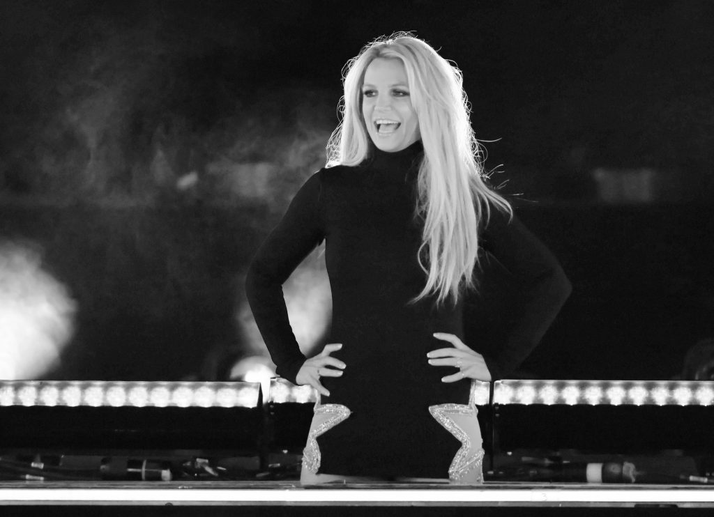 Britney Spears smiling on stage, in black and white