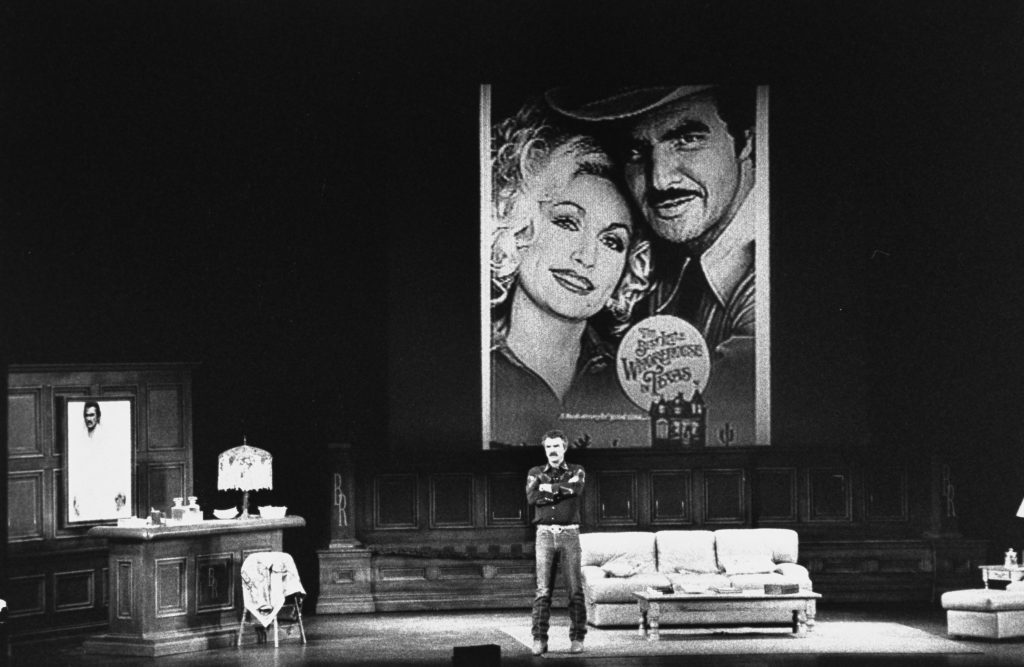 Burt Reynolds talking on stage with an image of him and Dolly Parton