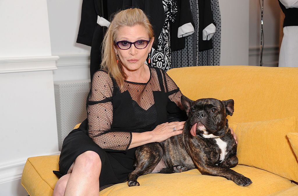 Carrie Fisher smiling, sitting with her dog on a yellow couch