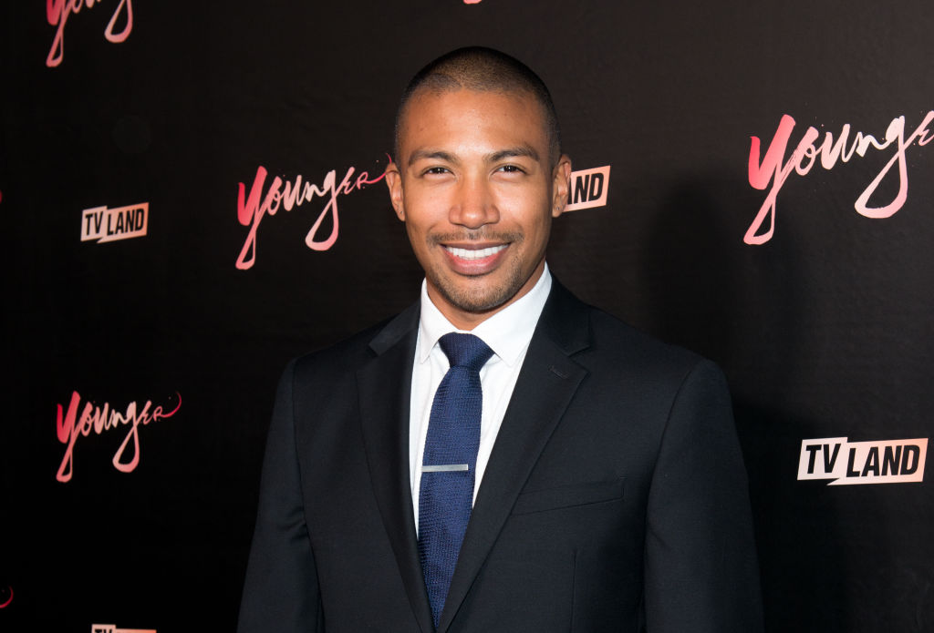 Charles Michael Davis smiling in front of a black background