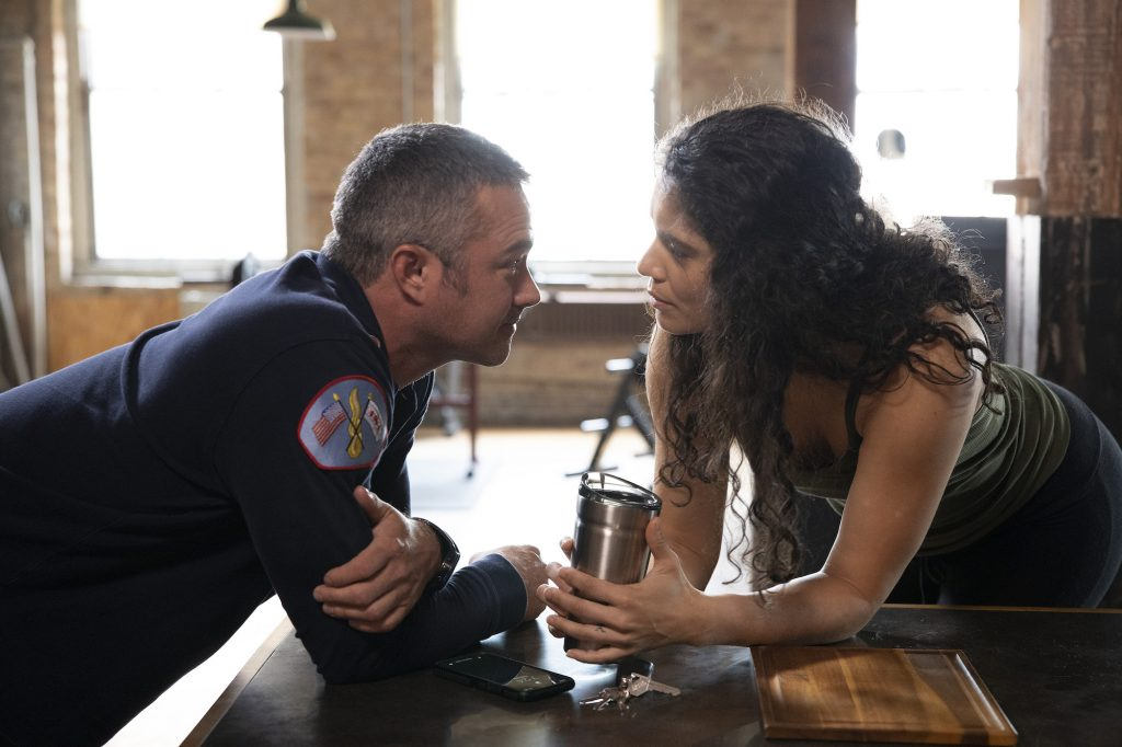 (L-R) Taylor Kinney as Lt. Kelly Severide, Miranda Rae Mayo as Stella Kidd leaning over a counter, looking at each other