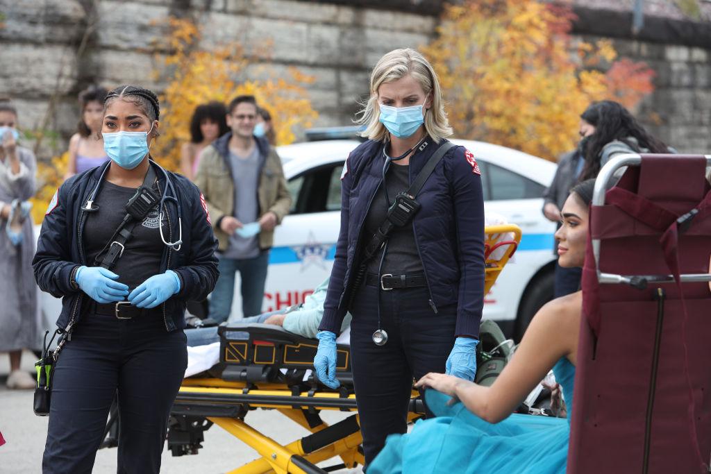 (L-R) Adriyan Rae as Gianna Mackey, Kara Killmer as Sylvie Brett wearing masks, standing outside in front of a small crowd