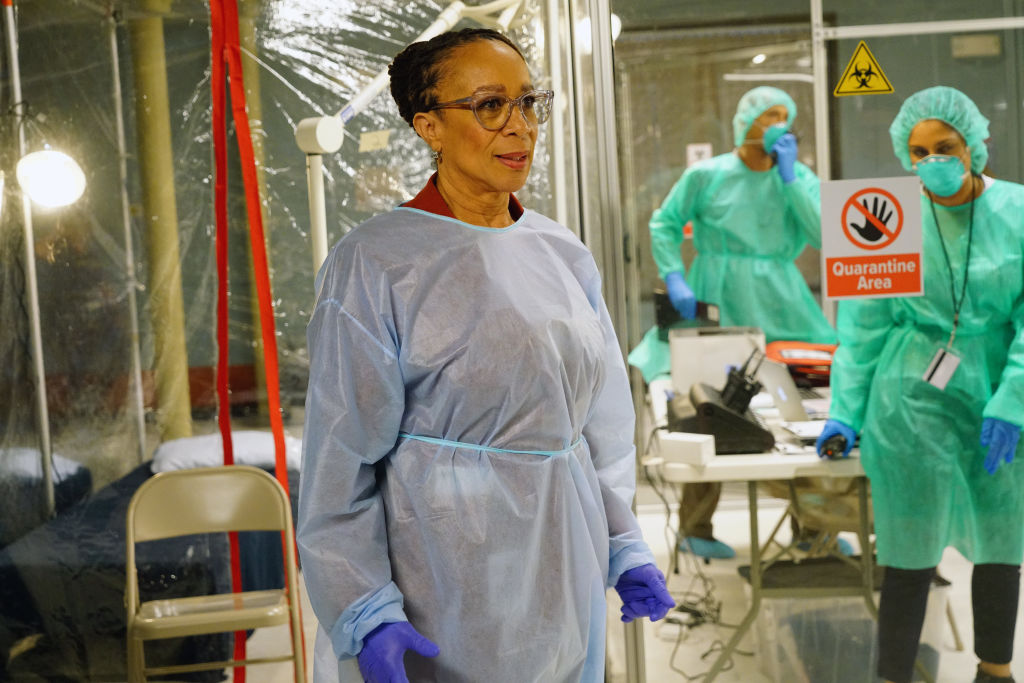 S. Epatha Merkerson as Sharon Goodwin in PPE, in front of a quarantine area