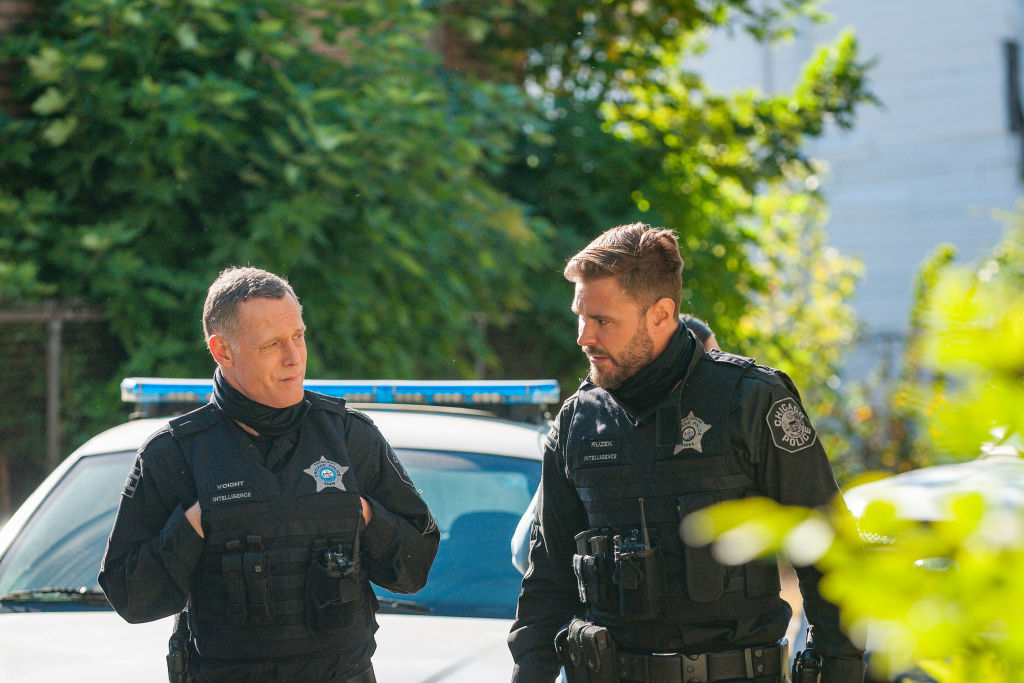 (L-R) Jason Beghe as Hank Voight, Patrick John Flueger as Adam Ruzek turned toward each other, in front of a cop car and tree