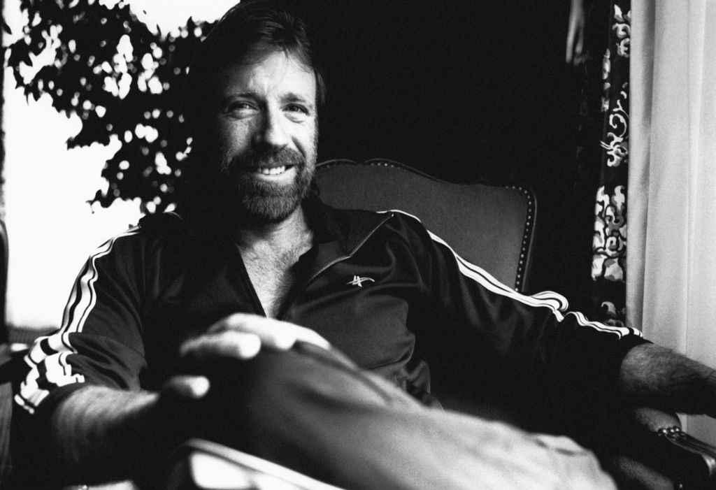 Chuck Norris smiling at the camera, in black and white