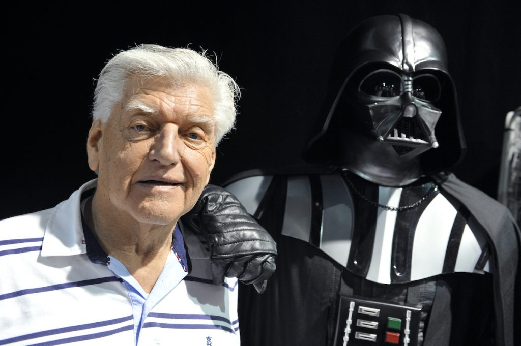 English actor David Prowse poses with a fan dressed up in a Darth Vader costume during a Star Wars convention on April 27, 2013 | Thierry Zoccolan/AFP via Getty Images