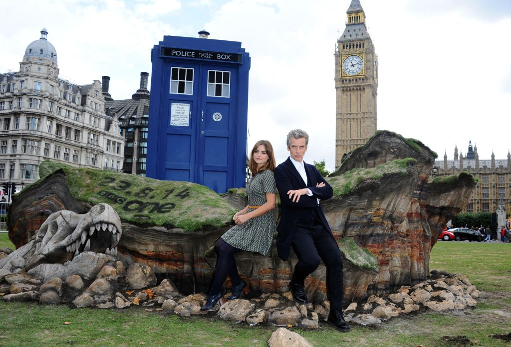 (L-R) Jenna Coleman and Peter Capaldi leaning against a rock, in front of a TARDIS