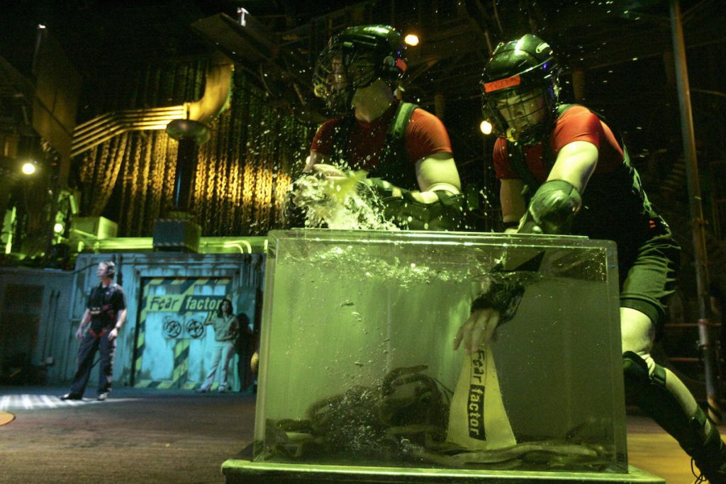 (L-R) Ray Beyda and Tyler Everett reaching into a tank full of snakes
