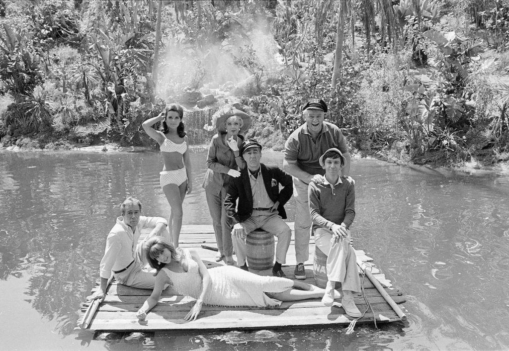 (L-R) Russell Johnson as The Professor, Roy Hinkley; Tina Louise as Ginger Grant; Dawn Wells as Mary Ann Summers; Natalie Schafer as Mrs. Lovey Howell; Jim Backus as Thurston Howell III; Alan Hale, Jr. as The Skipper (Jonas Grumby), and Bob Denver as Gilligan standing on a dock in a pond-like body of water