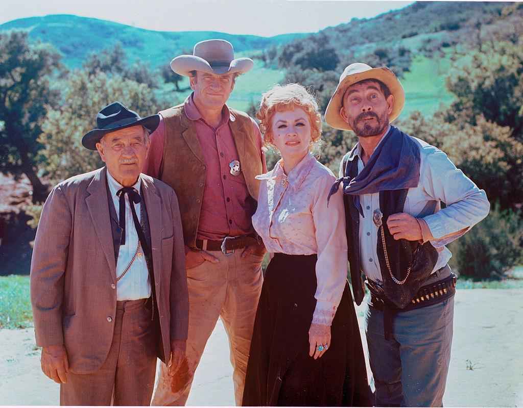 (L-R) Milburn Stone as Dr. Galen Adams, James Arness as U.S. Marshal Matt Dillon, Amanda Blake as Kitty Russell, and Ken Curtis as U.S. Deputy Marshal Festus Haggen