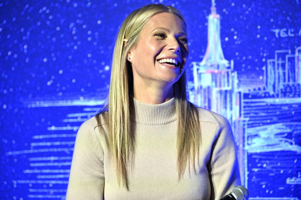 Gwyneth Paltrow laughing, looking to the right, sitting in front of a blue background