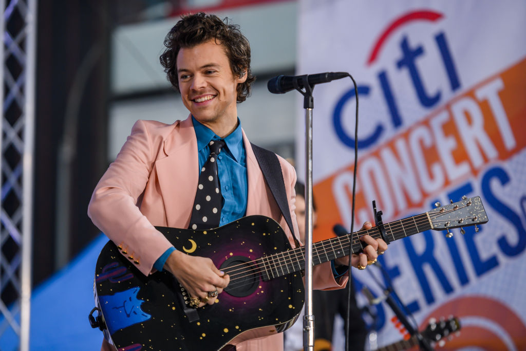 Harry Styles smiling on stage, holding a guitar