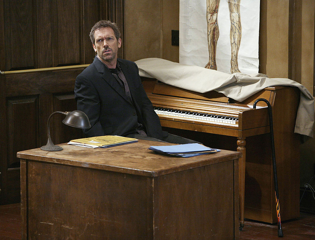 Hugh Laurie as Dr. Greg House sitting at a piano, turned to the side