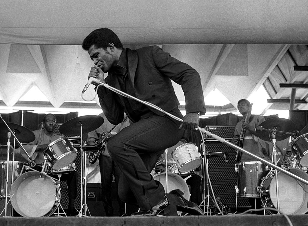James Brown singing into a microphone, bending down