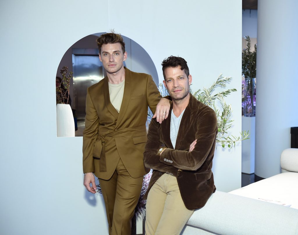 (L-R) Jeremiah Brent and Nate Berkus slightly smiling in a white room, leaning on a white couch