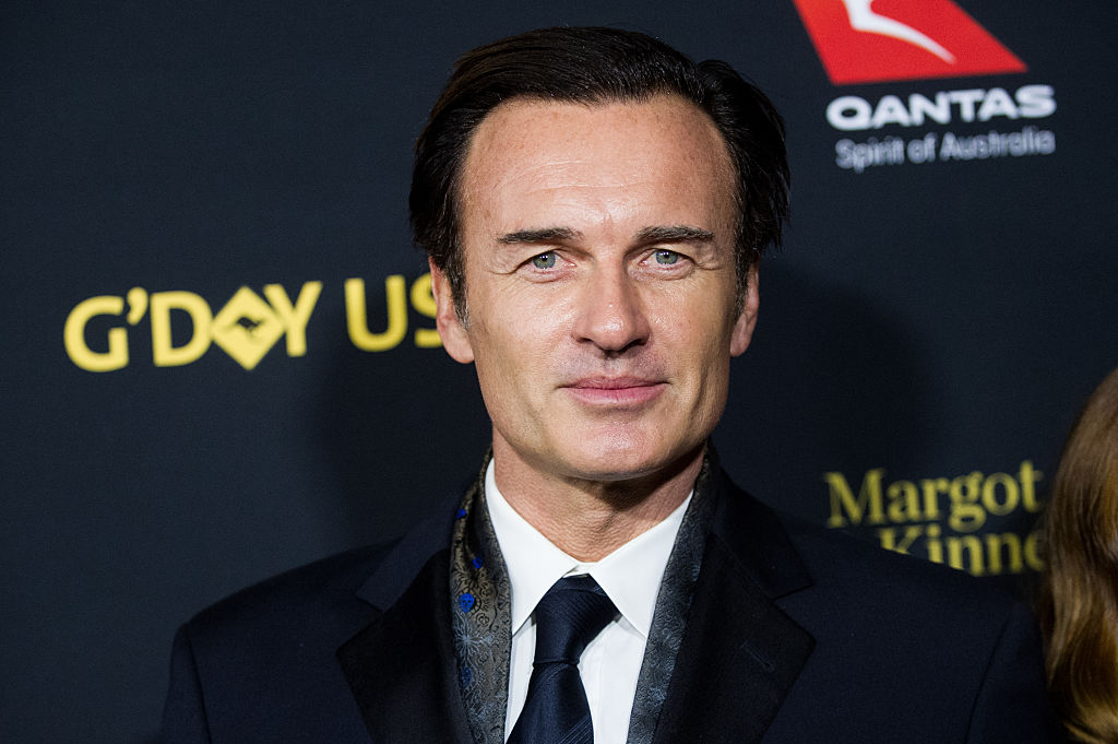 Julian McMahon smiling in front of a black background