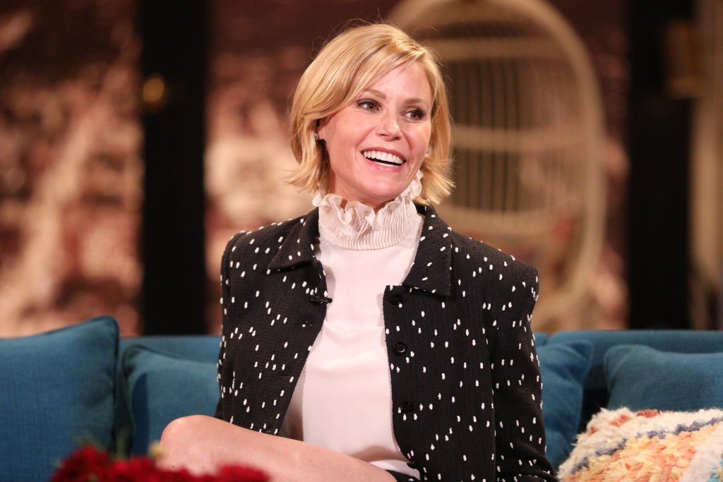 Julie Bowen smiling, sitting on a couch, in front of a blurred background